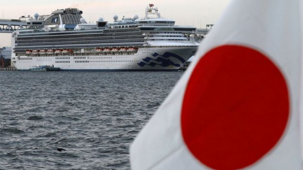 The cruise ship Diamond Princess is seen beside a Japanese flag as it lies at anchor while workers and officers prepare to transfer passengers tested positive for the novel coronavirus, at Daikoku Pier Cruise Terminal in Yokohama, south of Tokyo, Japan February 12, 2020
