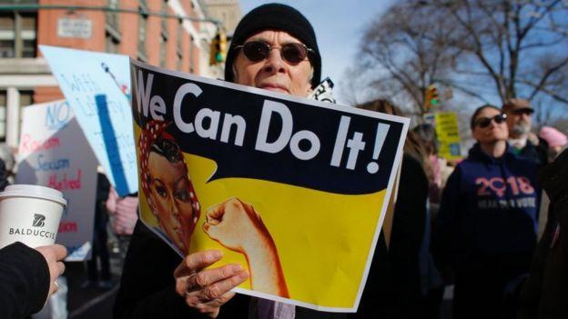 """Un hombre sostiene una pancarta con la clásica frase feminista """"We Can Do It"""" (Podemos hacerlo) en una protesta por el día de la mujer en Estados Unidos."""