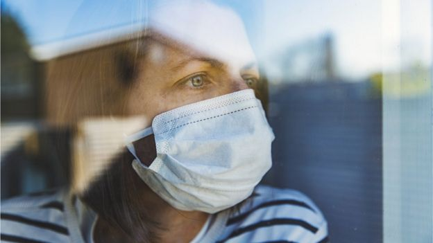 woman wearing mask looking out of window