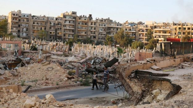 People walk near an over-crowded graveyard in the rebel held al-Shaar neighbourhood of Aleppo, Syria on 6 October 2016