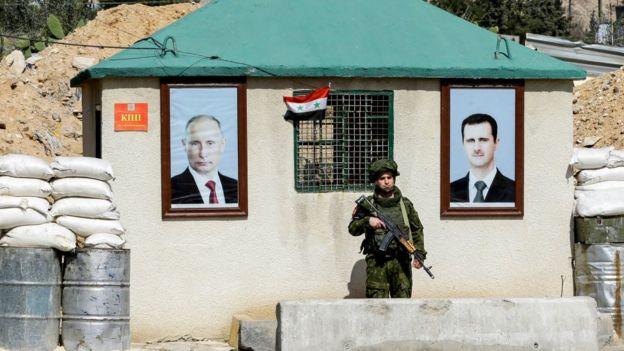 Afiches de Putin and al Asad en un punto de control militar.