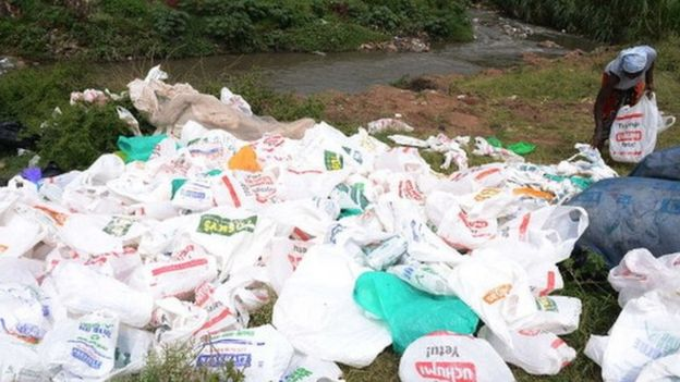 A woman sorts out used plastic bags for re-use at the shores of a river in Nairobi (24 June 2014)