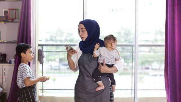 Una madre multitarea con teléfono inteligente y niños