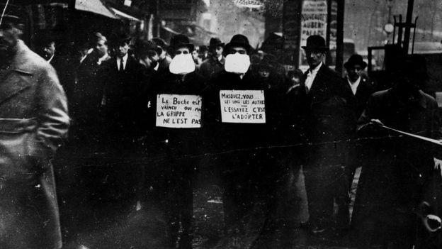 Homens usando máscara em foto antiga