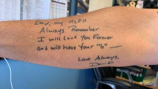 Braço de Dave Betz's, com tatuagem de mensagem que o filho escreveu no Dia dos Pais, na qual chama o pai de heroi e diz que vai amá-lo para sempre.