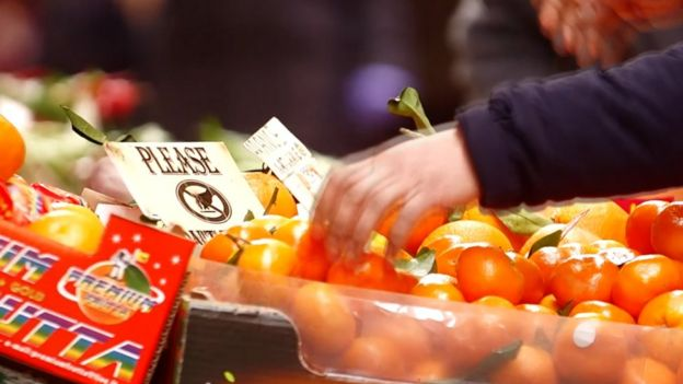 A hand touching oranges at a market