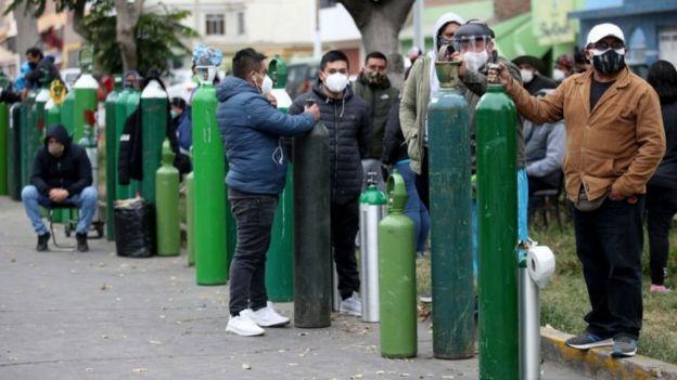 Gente haciendo fila con balones de oxígeno