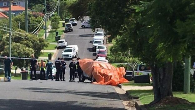 Scene from Camp Hill in Brisbane with police waiting around a cordon at the site of a car fire