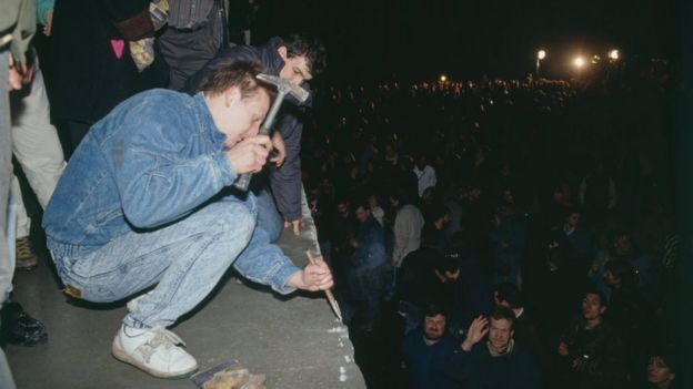 Un joven con un martillo sobre el Muro de Berlín.