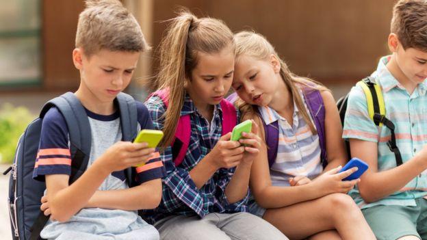 Niños sentados usando sus teléfonos celulares
