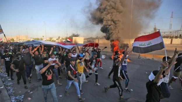 محتجون يرفعون العلم العراقي في وسط بغداد.