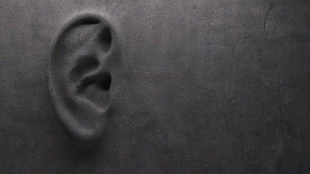Una pared gris de concreto con una oreja esculpida en ella