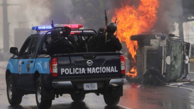 Una patrulla de la policía pasa frente a un auto quemado.