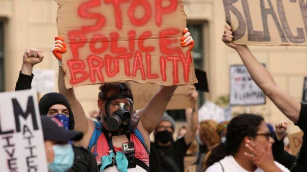 """متظاهرون يحملون لافتات كتب عليها """"أوقفوا وحشية الشرطة"""""""