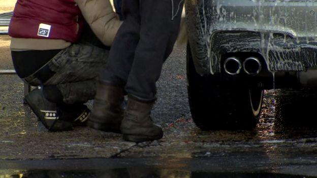 Hombres en un lavadero de autos, sólo piernas a la vista