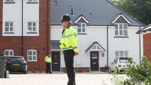 Police officer guards a house in Amesbury