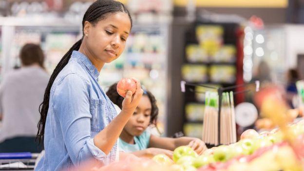 mulher e criança examinam frutas no supermercado