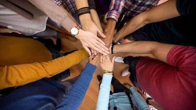 Imagen que muestra las manos juntas de personas de distintos tonos de piel.