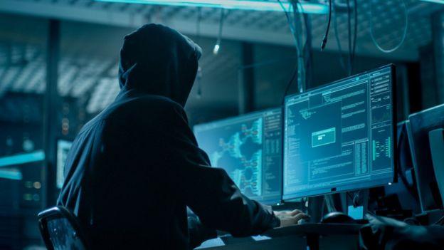 Hombre con capucha y de espaldas manipulando ordenador.