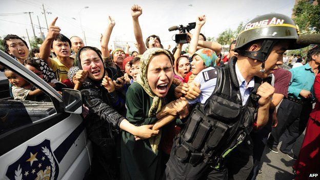 Uighur women grab a riot policemen as they protest in Urumqi in China's far west Xinjiang province on July 7, 2009