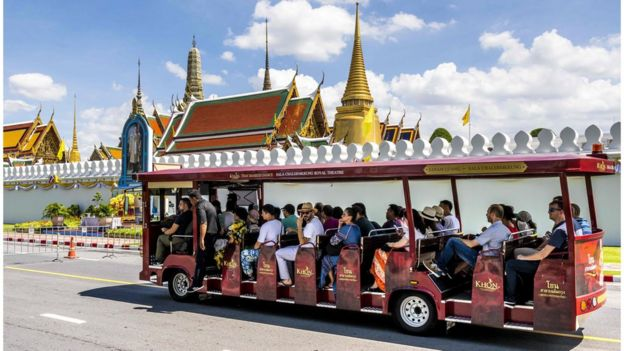 Tourists ride a bus in front of the Thai Royal Palace in Bangkok on September 12, 2019.