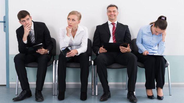 Cuatro personas sentadas esperando por una entrevista de trabajo