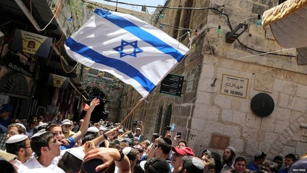 Young people wave an Israeli flag as they celebrate Jerusalem Day