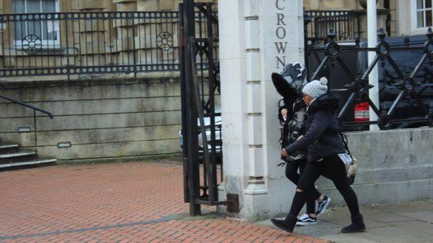 Ms Cordice, wearing hood, enters court