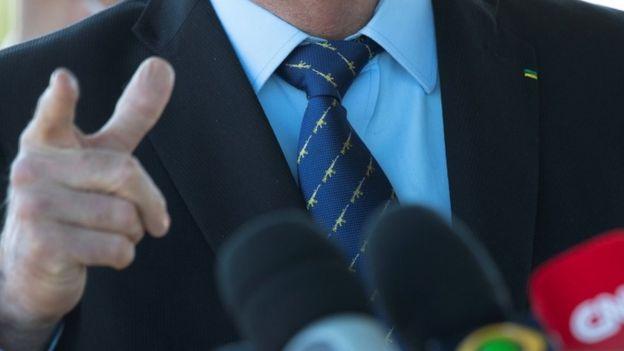Dedo em riste de Bolsonaro enquanto fala, com microfones de canais de tv em frente