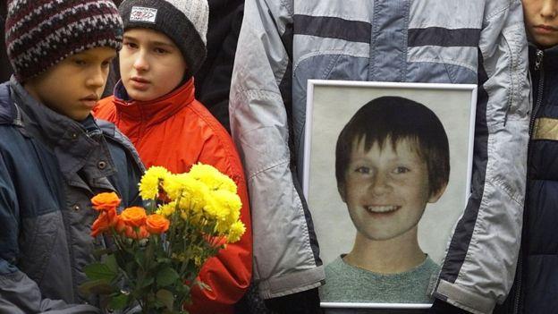 Мальчик с цветами и портретом погибшего ребенка