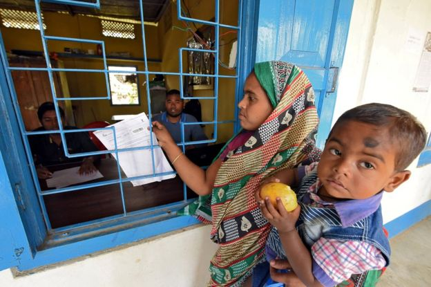 A woman carrying her son arrives to check her name on the draft list of the National Register of Citizens (NRC) centre in Chandamari, Assam.