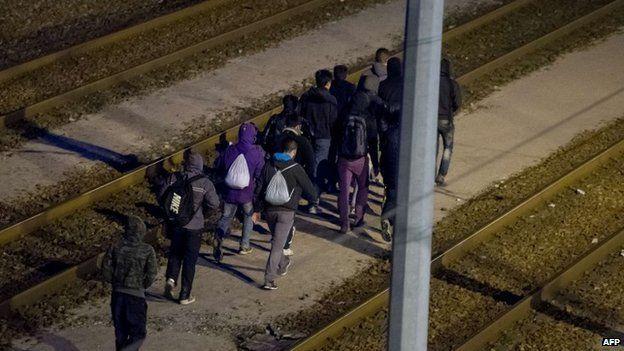 Migrants walking along rail tracks towards the Channel Tunnel