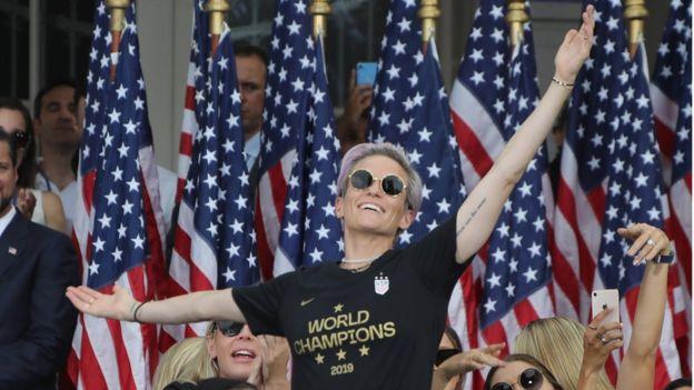 Rapinoe diante de bandeiras americanas