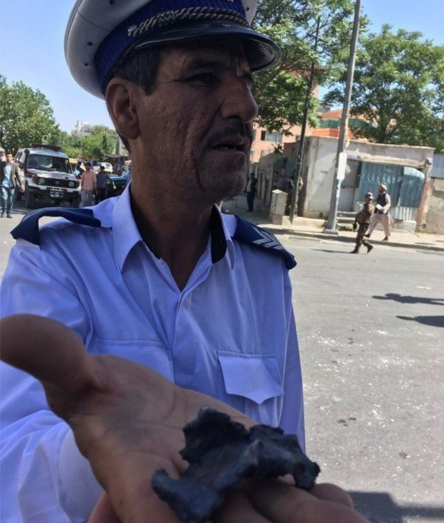 Un policía muestra a nuestro corresponsal un pedazo de metralla de la explosión