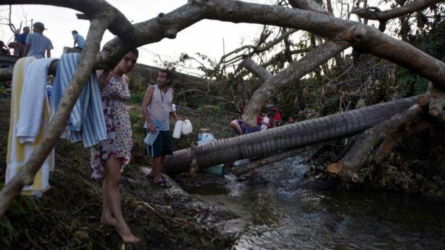 Una familia se abastece de agua en una quebrada