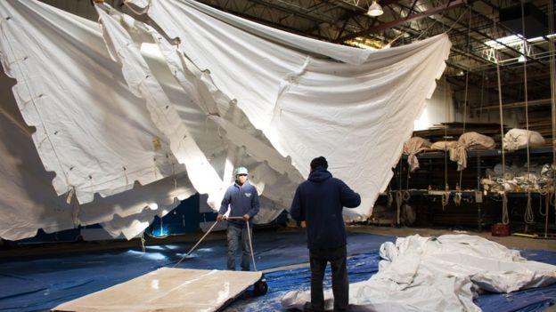 Trabalhadores limpam tenda que será alugada para evento