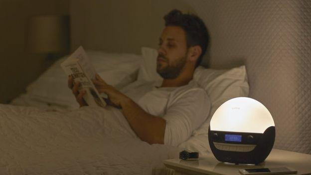 Hombre en la cama con despertador del amanecer