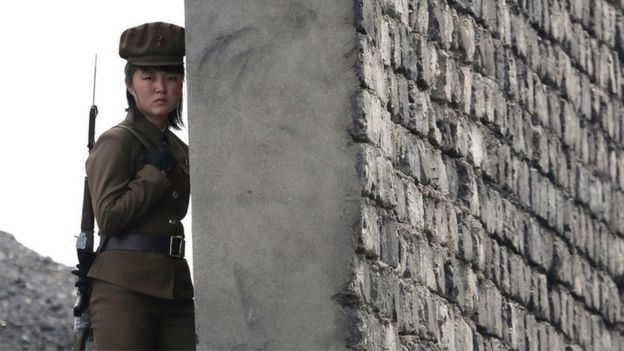 A North Korea woman soldier patrols the bank of the Yalu River which separates the North Korean town of Sinuiju from the Chinese border town of Dandong