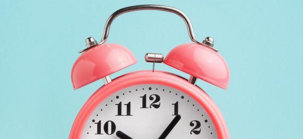 Pink alarm clock on turquoise-blue background