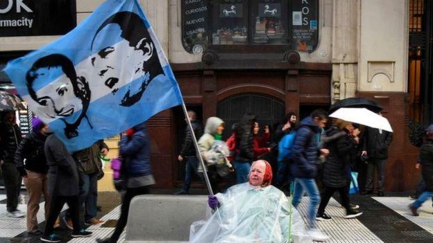 Una mujer ondea bandera con los rostros de Juan Domingo Perón y Evita durante una marcha a favor del aumento del sueldo de los maestros y en contra de los recortes a las universidades públicas de Argentina, en Buenos Aires, el 30 de agosto de 2018.