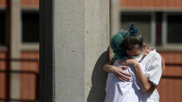 Medical workers hug each other outside the emergency rooms at Severo Ochoa Hospital during the coronavirus disease in Spain