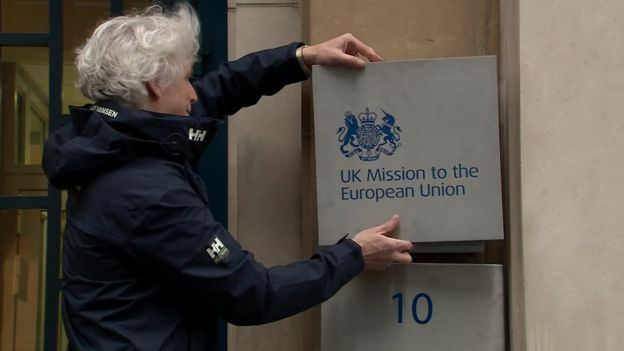 A man changing the sign outside the UK government delegation to the EU, which changed its name to UK Mission to the European Union