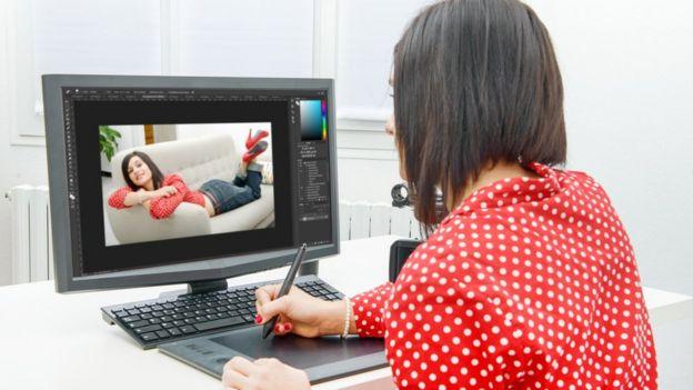 Mujer frente a la computadora editando una fotografía.