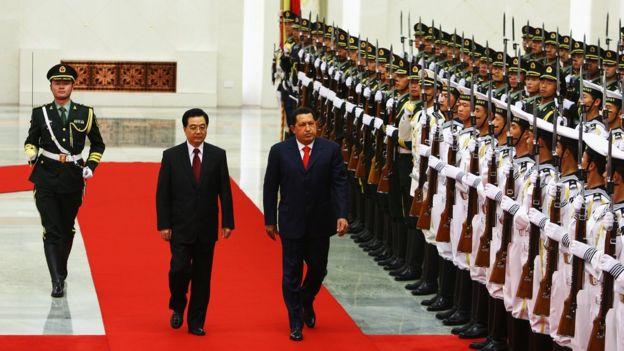 Chavez e Hu Jintao caminham em tapete vermelho com expressão facil séria, observados por militares em cerimônia