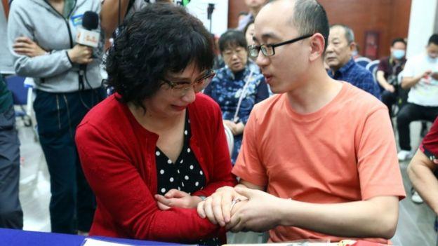 Li Jingzhi se toma de las manos con su hijo.