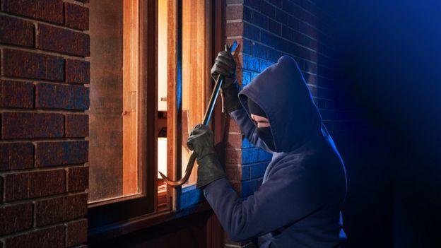 Ladrón intentando entrar a una casa forzando la ventana
