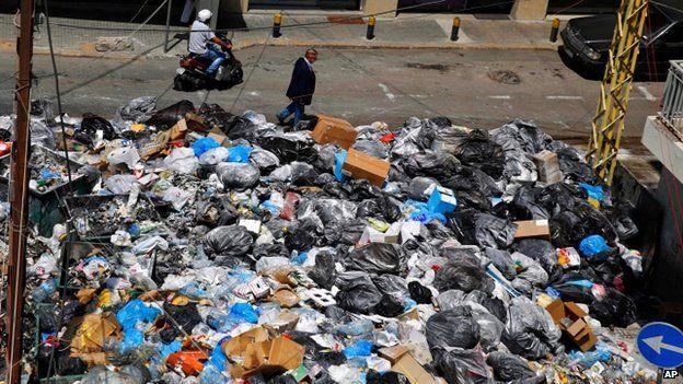 Man walks past masses of rubbish in Beirut street