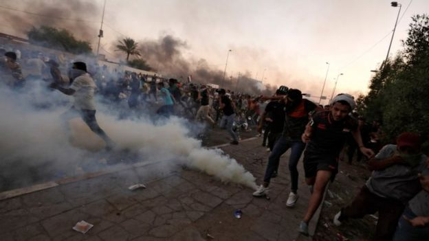 Protesters run away after security forces use tear gas in Baghdad, Iraq. Photo: 5 October 2019