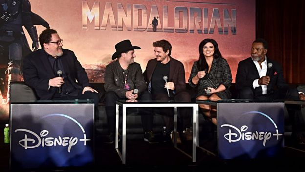 "WEST HOLLYWOOD, CALIFORNIA - OCTOBER 19: (L-R) Executive producers/writers Jon Favreau, Dave Filoni, actors Pedro Pascal, Gina Carano and Carl Weathers of Lucasfilm's ""The Mandalorian"" at the Disney+ Global Press Day on October 19, 2019 in Los Angeles, California. ""The Mandalorian"" series will stream exclusively on Disney+ when the service launches on November 12. (Photo by Alberto E. Rodriguez/Getty Images for Disney)"