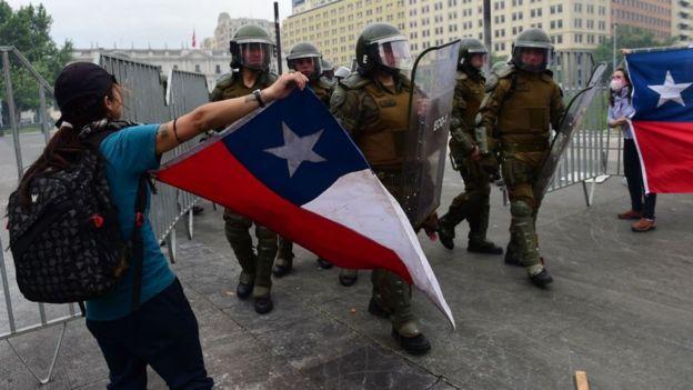 Manifestantes con banderas chilenas frente a los policías chilenos.
